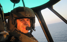 The Chief of the Defence Staff, General Tom Lawson, pilots HMCS Regina's Sea King Helicopter while visiting Canadian Armed Forces personnel deployed in the Arabian Sea.