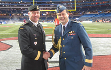 General Tom Lawson (right), the Chief of the Defence Staff, greets Brigadier-General Omer Lavoie (left), Commander of Land Forces Central Area, on the sidelines of the field during the 2012 Grey Cup weekend in Toronto.