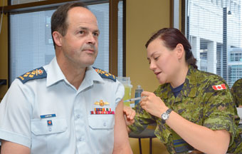 Gen Tom Lawson, CDS, receives the annual influenza shot from Lt Stephanie Chan, Canadian Forces Health Services Centre (Ottawa), at NDHQ.
