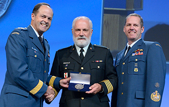 General Tom Lawson (left), Chief of the Defence Staff, accompanied by Chief Warrant Officer Kevin West (right), Canadian Forces Chief Warrant Officer, presents Dr Louis Francescutti, Honorary Colonel for Royal Canadian Medical Services and President of the Canadian Medical Association (CMA), with the Canadian Forces Medallion for Distinguished Service, during the 147th CMA Annual Meeting held at the Ottawa Convention Centre in Ottawa, Ontario, on August 19, 2014.