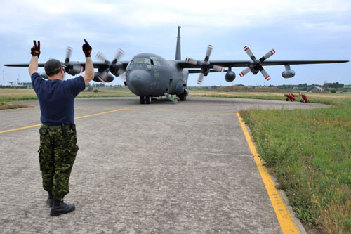 Trapani, Italy — Master-Corporal William Stamper, Task Force Libeccio Avionics Technician, marshals a CC-130 Hercules prior to takeoff during Operation Mobile in Trapani, Italy on May 24, 2011.