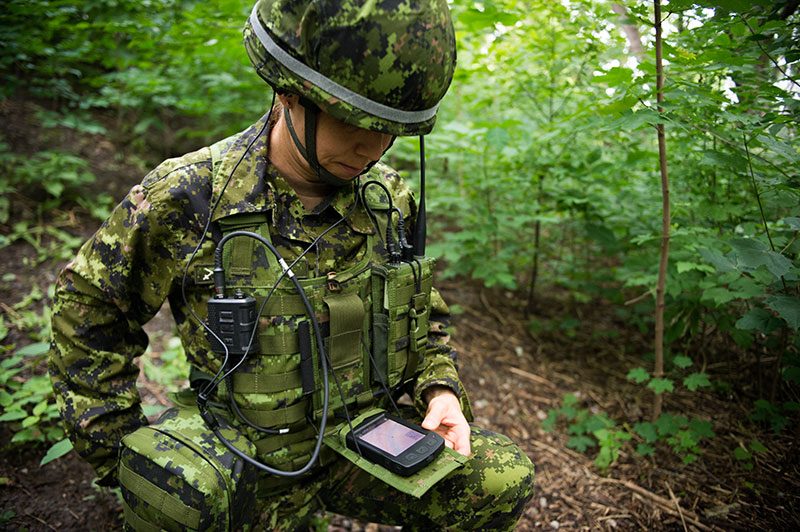 A Canadian Armed Forces Soldier demonstrates a suite of military equipment for the Integrated Soldier System Project