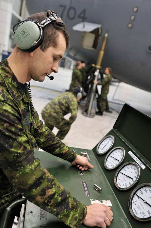Master Corporal Mieszco Jachira-Cmolassowski operates a hydraulic pump station while a CC-177 Globemaster is being lifted at hangar 1 at Canadian Forces Base Trenton during a periodical maintenance called Home Station Check (HSC). Photo: Sgt Gaétan Racine, Canadian Forces Combat Camera