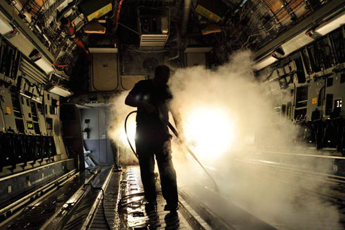 Aircraft Structures Technician Corporal Michael Glennon uses steam to clean a CC-177 floor during a Home Station Check (HSC). Photo: Sgt Gaétan Racine, Canadian Forces Combat Camera
