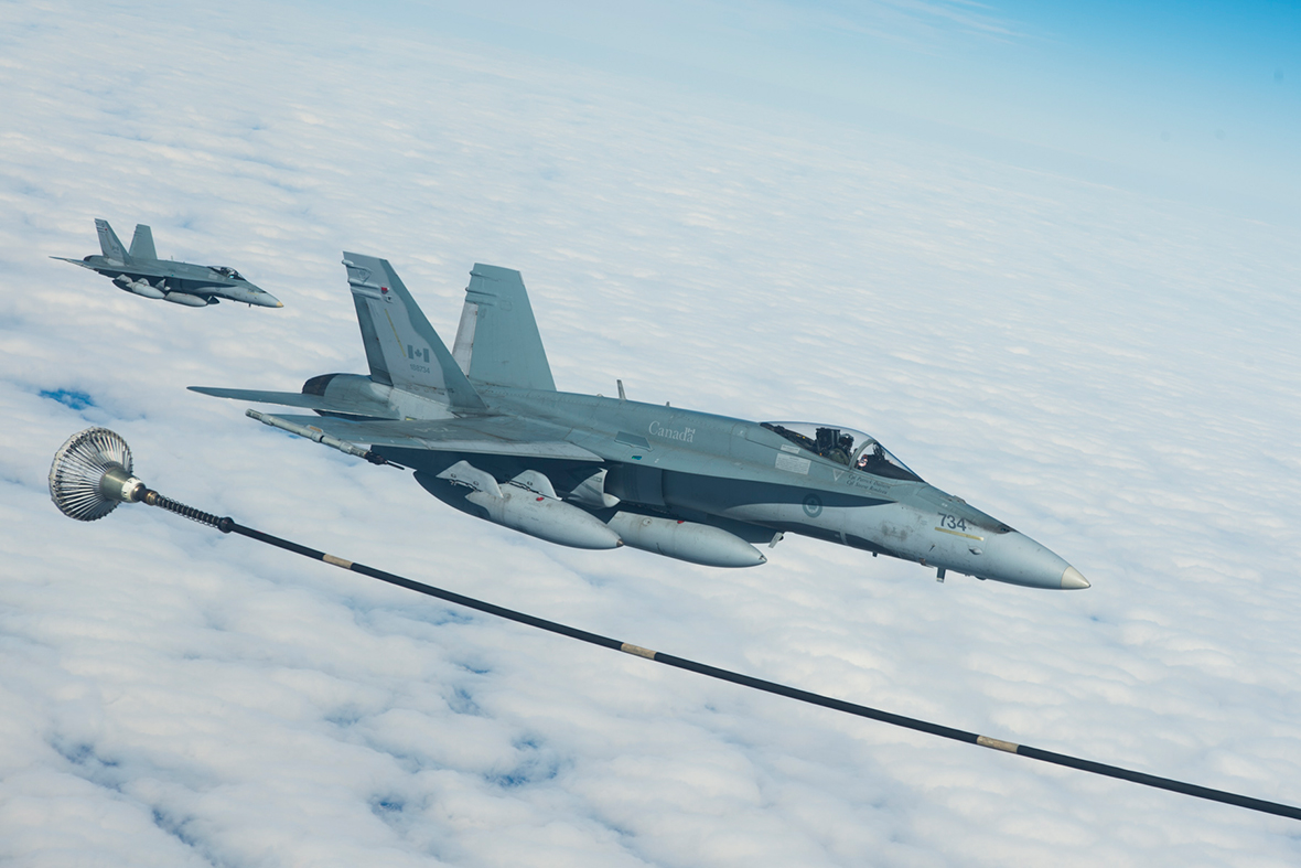 Two CF-18 Hornets from 425 Tactical Fighter Squadron in Bagotville, Québec prepare to receive fuel from a CC-150 Polaris air-to-air refueling tanker while on route to Keflavik, Iceland in support of NATO reassurance measures on April 28, 2014. Photo: Master Corporal Roy MacLellan, 8 Wing Imaging