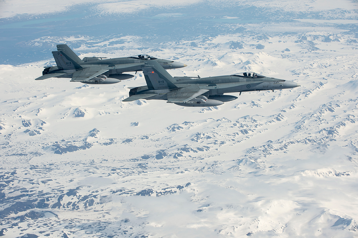 Two CF-18 Hornets from 425 Tactical Fighter Squadron in Bagotville, Québec fly over the mountains of Iceland after departing Keflavik, Iceland in support of NATO reassurance measures on May 1, 2014. Photo: Master Corporal Roy MacLellan, 8 Wing Imaging