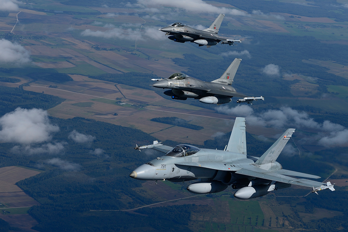 A CF-18 Hornet from the Canadian Air Task Force Lithuania flies beside two Portuguese F16 Fighting Falcons over Lithuania on September 15, 2014 for the NATO Baltic Air Policing Block 36 during Operation REASSURANCE.