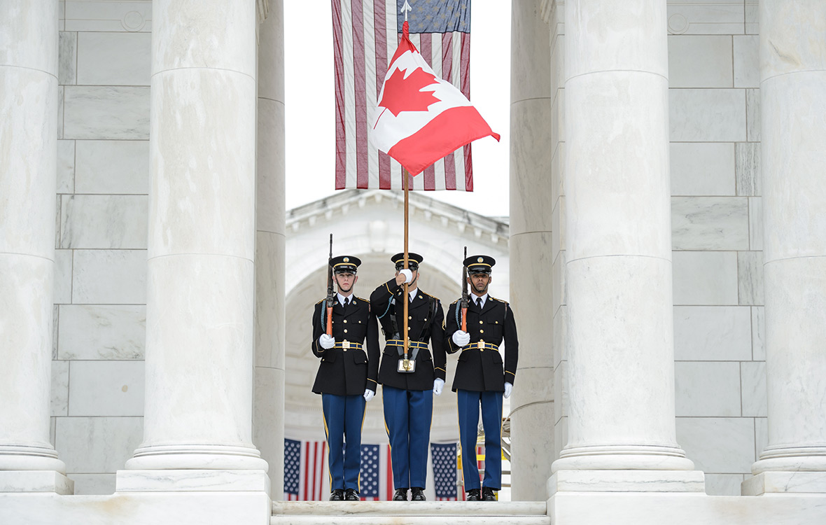 American soliders stand at attention with the Canadian flag during a wreath-laying ceremony at Arlington Cemetery in Virginia on May 23rd, 2017. Photo credit: Corporal Chase Miller Canadian Forces Support Unit (Ottawa) - Imaging Services