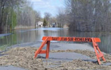 A flooded road with an orange barricade.