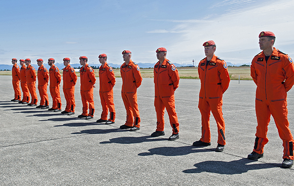 Twelve search and rescue technicians stand on parade during the June 11, 2015, graduation ceremony of Canadian Forces School of Search and Rescue qualification level 5A, search and rescue technician course 48, at 19 Wing Comox, British Columbia. To arrive here, they have undergone 11 months of intense training at locations including Jarvis Lake, Hinton, Alberta; and Eloy, Arizona. SAR techs, whether parachuting, rappelling, climbing or scuba diving, respond to any nautical, land or aviation-based incident throughout Canada, often in the harshest of conditions. SAR techs are fully qualified paramedics and first responders. PHOTO: Sergeant Halina Folfas