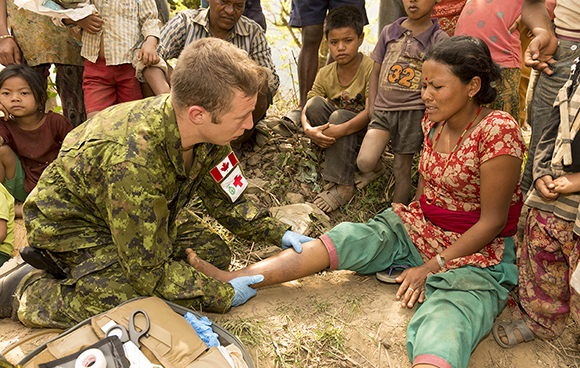 A villager receives treatment by Master Corporal Nicholas Cappelli Horth, a DART medical technician, in the village of Kodari in Sindhupalchok District, Nepal on May 6, 2015. Photo: MCpl Cynthia Wilkinson, Canadian Forces Joint Imagery Center DA50-2015-0001-039