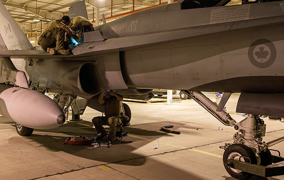 Aviation Systems Technicians with Air Task Force - Iraq work through the night maintaining a CF-188 Hornet fighter jet at Camp Patrice Vincent, Kuwait during Operation IMPACT on 26 March 2015. Photo: OP Impact, DND GD2015-0106-16
