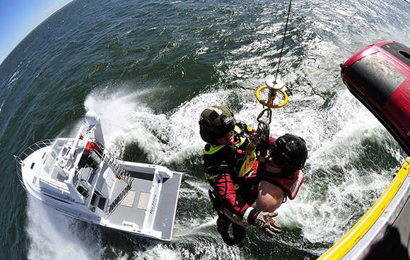 Sergeant Terrence Grandy (left) and Master Corporal Chris Martin (right) both Search and Rescue Technicians, are being hoisted up into a CH-149 Cormorant helicopter from a boat over the Northumberland Strait off of Prince Edward Island during a boat camp exercise on June 15, 2015. Photo: Master Corporal Johanie Maheu, 14 Wing Imaging – Greenwood, NS GD2015-0334-11