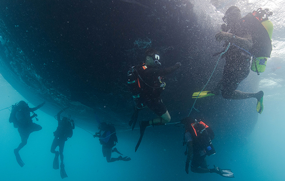 Leading Seaman Zack Verdun, Clearance Diver from Fleet Diving Unit (Atlantic), provides direction to Caribbean divers as they practice a necklace search under United States Army Ship Aldie during Exercise TRADEWINDS 15 in St Kitts and Nevis on June 5, 2015. Photo: Sgt Yannick Bédard, Canadian Forces Combat Camera. IS01-2015-0005-050