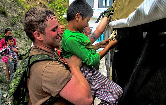 Bombardier Travis Richardson, a member of Canada's Disaster Assistance Response Team, holds a child so he can tie up a tent flap on May 13, 2015 in Sindhupalchok Region, Nepal.Photo: Captain Clayton Myhill IS09-2015-0031-012