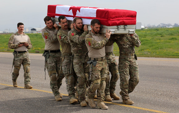 Pallbearers from the Canadian Special Operations Regiment (CSOR) carry the casket of their fallen comrade, Sergeant Andrew Joseph Doiron, during the ramp ceremony at Erbil International Airport, Iraq, on March 8, 2015. Photo: OP Impact, DND