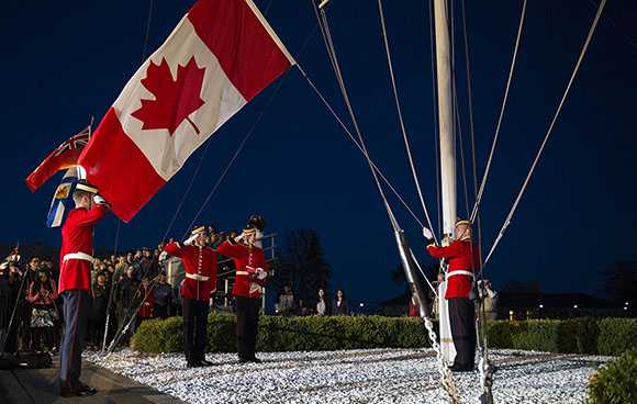 Cadets salute during the lowering of the National flag marking the end of the Sunset Ceremony held at Royal Military College of Canada, Kingston ON, on May 14, 2015