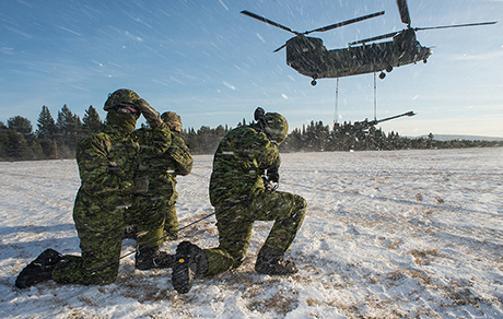 Members of the 5th Canadian Mechanized Brigade Group shield themselves from the take off of a CH-147 Chinook helicopter with a M777 Howitzer artillery piece in the 430 Tactical Helicopter Squadron's tactical landing zone at Valcartier Base, Courcelette, QC on December 2, 2014 during a helicopter operations course. Photo: Corporal Nicolas Tremblay, Valcartier Imaging Section