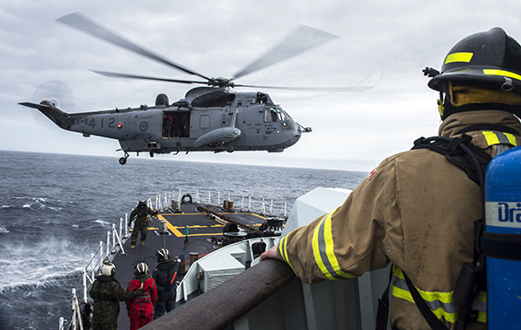 Her Majesty's Canadian Ship FREDERICTON's CH-124 Sea King helicopter prepares to hoist a crew member from the foc'sle as part of a training exercise while transiting to the Mediterranean Sea for Operation REASSURANCE on January 3, 2015. Photo: Maritime Task Force - OP REASSURANCE HS2015-C001-020
