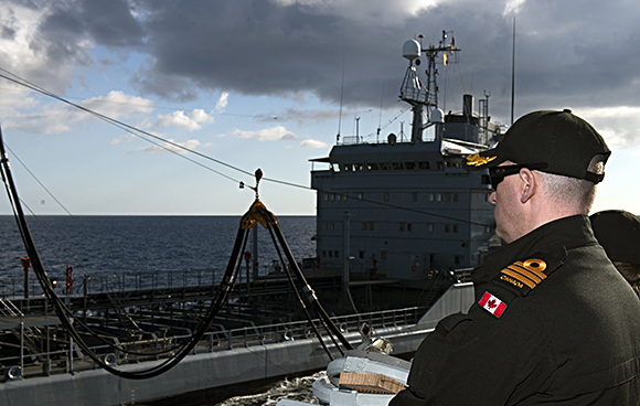 Commander Jeff Murray, Commanding Officer of Her Majesty's Canadian Ship FREDERICTON, controls the ship's movements from the bridge wing during a replenishment at sea with German supply ship FGS SPESSART on Operation REASSURANCE, January 18, 2015. Photo: Maritime Task Force - OP Reassurance, DND