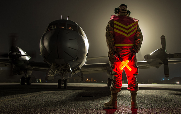 A Royal Canadian Air Force technician guides a CP-140 Aurora to its parking area during Operation IMPACT in Kuwait on February 5, 2015. Photo: Canadian Forces Combat Camera, DND