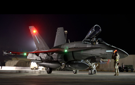 A Canadian Armed Forces member guides a CF-18 Hornet to the runway for a night mission in Kuwait during Operation Impact on November 6, 2014. PHOTO: Canadian Forces Combat Camera, DND