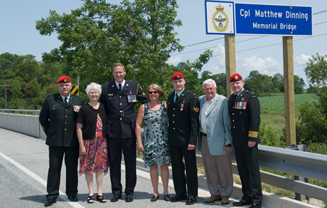 Colonel (Col) Robert Delaney, Canadian Forces (CF) Provost Marshal and Commander of the CF Military Police (MP) Group,  and members of the Dinning family pose at the  bridge dedicated to Corporal (Cpl) Matthew Dinning.  The ceremony to dedicate the Highway 21 bridge over Clark Creek, Bruce County in honour of Cpl Dinning was held on July 18th, 2014.  Cpl Matthew Dinning, an MP, was killed in Afghanistan in April 22nd, 2006.  Photo taken at the Royal Canadian Legion in Wingham, Ontario. Photo:  Cpl Katharine Quint, CFB Borden Imaging