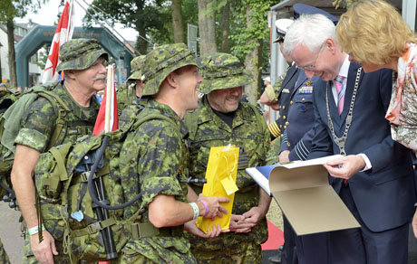 Chief Warrant Officer Keith Jones (left), Sergeant Major of Joint Task Force (JTF) Nijmegen 2014, Brigadier-General Alain Pelletier (second from left), Commander of JTF Nijmegen 2014 and Captain (Navy) Randy Caspick present Hans Verheijen, Mayor of Wijchen, Netherlands and his wife a gift on behalf of the Canadian Armed Forces JTF Nijmegen 2014 team on July 16, 2014, the second official day of the Nijmegen Marches. Photo: Cpl Andrew Wesley, Joint Task Force Nijmegen 2014