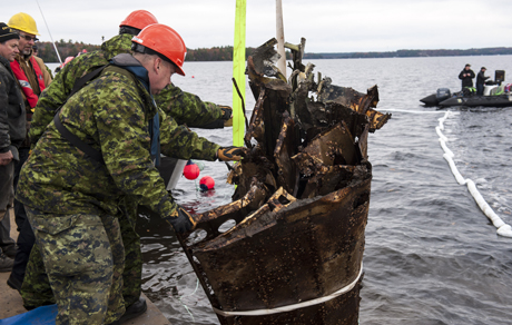 Canadian Armed Forces members carefully maneuver one of the wings of the Northrop Nomad aircraft onto the barge from Lake Muskoka on October 27, 2014 after decades underwater. Photo: MCpl Roy MacLellan, 8 Wing Imaging, TN2014-0669-J0016