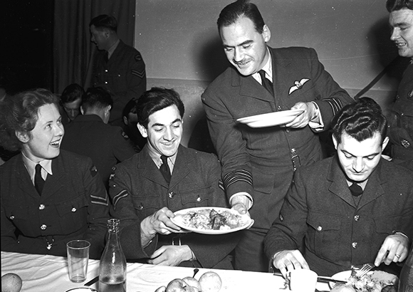 The officers and senior non-commissioned members serving the junior non-commissioned members with their Christmas dinner is a long-standing military tradition. In this photo taken on December 28, 1942, at 425 Squadron, Group Captain J. Plan serves Corporal M. Demers. PHOTO: DND