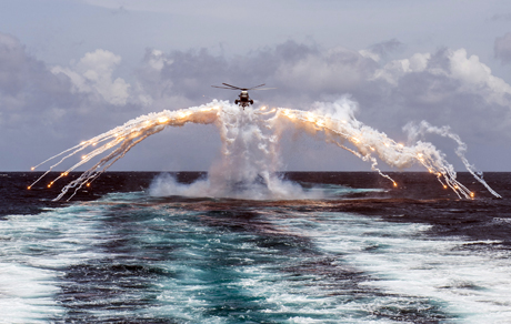Her Majesty's Canadian Ship REGINA's CH-124 Sea King helicopter deploys flares during a routine flight operation in the Indian Ocean on August 14, 2014. Photo: Cpl Michael Bastien, MARPAC Imaging Services