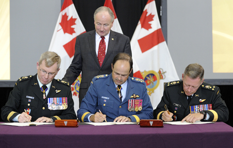 Under the watchful eye of the Minister of National Defence, Rob Nicholson, from left to right, LGen Stuart Beare, outgoing Commander, General Tom Lawson, CDS, LGen Jonathan Vance, incoming Commander Canadian Joint Operations Command, sign the change of command scroll on September 9, 2014, in Ottawa. Photo: Cpl Pierre Habib
