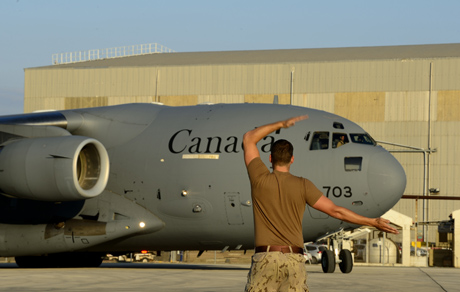 A Canadian Armed Forces Member guides a CC-177 Globemaster airplane on an airfield in the Mediterranean, during Operation Impact on September 11, 2014. Photo: MCpl Patrick Blanchard, Canadian Forces Combat Camera