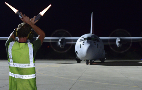 A technician signals a CC-130J Hercules aircraft to stop on an airfield in the Mediterranean during Operation IMPACT on September 6, 2014. Photo: MCpl Patrick Blanchard, Canadian Forces Combat Camera
