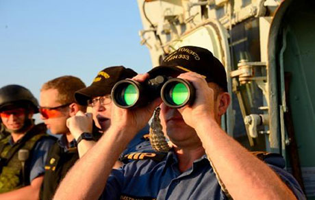 Commanding Officer of Her Majesty's Canadian Ship TORONTO, Commander Jason Armstrong uses binoculars on the bridge wing of his ship...