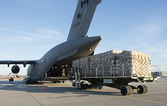 Master Corporal (MCpl) Massie guides the K-50 Cargo loader into position to start the loading process of non-lethal humanitarian aid bound for Kuwait and Iraq, at CFB Trenton, Ontario on January 22, 2015. Photo: Cpl Rob Stanley, 8 Wing Imaging