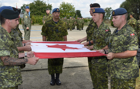 Members of the Canadian Air Task Force (ATF) Romania fold the Canadian Flag at the closeout ceremony for the ATF's mission in Romania on August 22, 2014 in Campia Turzii during Operation REASSURANCE. Photo: Cpl Jean Archambault, ATF 1401 Imagery Technician.