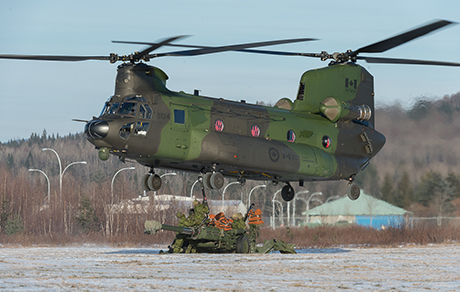 Members of the 5th Canadian Mechanized Brigade Group complete the hook up and marshaling operations during a helicopter operations course with a CH-147 Chinook helicopter and an M777 Howitzer artillery piece in the 430 Tactical Helicopter Squadron's tactical landing zone at Valcartier Base, Courcelette, QC on December 2, 2014.  Photo: Cpl Nathan Moulton, Valcartier Imagery Section.