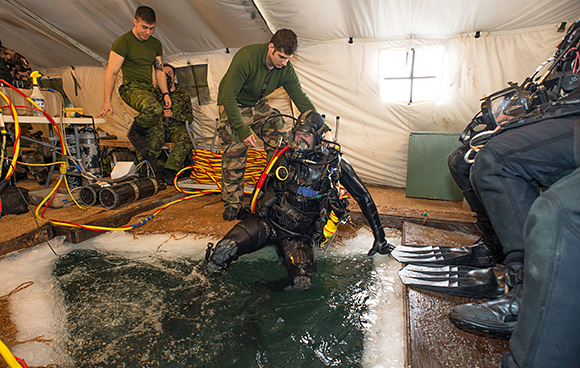 Sergeant Mathieu Torah, a combat diver with the French armed forces, helps Corporal Pierre-Luc Auger from 5e Régiment de génie de combat, out of the water following an ice dive in Deschambault-Grondines, Quebec on February 19, 2015 during Exercise ROGUISH BUOY. Photo: Cpl Genevieve Lapointe, Valcartier Imaging Section