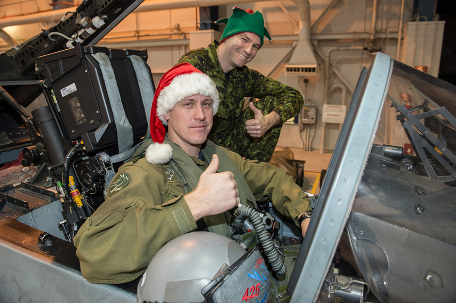 "Captain Denis ""Cheech"" Beaulieu (foreground), from 425 Tactical Fighter Squadron at 3 Wing Bagotville, Quebec, is one of Santa's escort pilots for 2014 and Master Corporal Daniel Boucher is his crew chief. PHOTO: Leading Seaman Alex Roy"