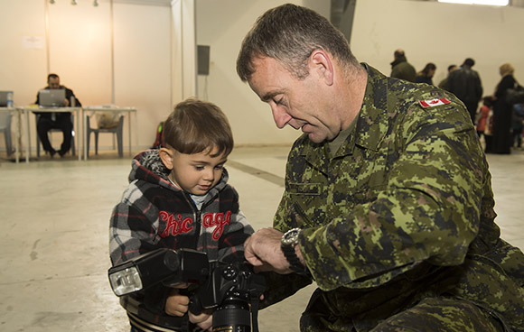 Master Corporal Bernie Kuhn, an imagery technician based in Ottawa, shows Mohamed the photos he took during the day at the processing centre in Amman, Jordan on December 13, 2015 during Operation PROVISION. Photo: Cpl Mohamed Anis Assari, AETE AE12-2015-9999-0002