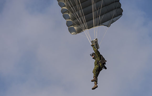 A member of 3R22eR steers a square parachute toward the landing zone during a para exercise at Nowa Dęba Training Center in Nowa Dęba, Poland on December 5, 2015 during Operation REASSURANCE. Photo: Corporal Nathan Moulton, Land Task Force Imagery, OP REASSURANCE RP001-2015-0062-045