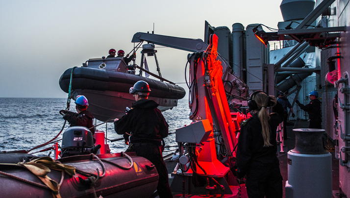 Members of Her Majesty's Canadian Ship (HMCS) FREDERICTON launch the rigid hull inflatable boat (RHIB) during a night time personnel exchange during Operation REASSURANCE, May 10, 2016. Photo: Corporal Anthony Chand, Formation Imagery Services HS2016-A083-003