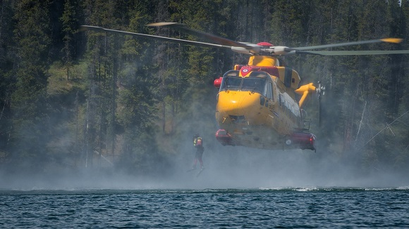 A student from the Canadian Forces School of Search and Rescue Technician course 49 jumps from a CH-149 Cormorant helicopter into Jarvis Lake in Alberta on June 5, 2016.  Photo: Corporal PJJ Létourneau, 19 Wing Imaging CX02-2016-0182-070