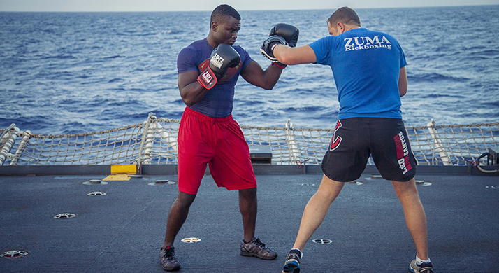 A Petty Officer 2nd Class demonstrates proper technique for a left hook with an Ordinary Seaman on board Her Majesty's Canadian Ship Vancouver in the Pacific Ocean during RIMPAC 16 on July 17, 2016. Photo: HMCS Vancouver UR01-2016-0718-003