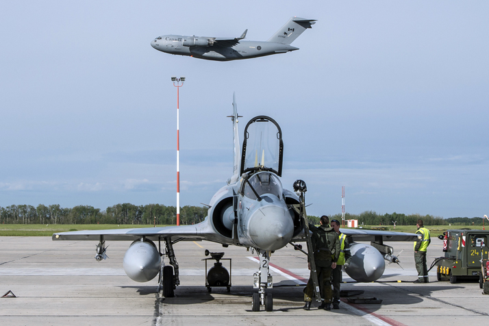 Air crew for the French Air Force prepare for their next mission while a Royal Canadian Air Force CC-177 Globemaster takes off from the runway behind them during Exercise MAPLE FLAG at 4 Wing Cold Lake, Alberta on June 1, 2016. Photo: Cpl Manuela Berger, 4 Wing Imaging CK01-2016-0510-023