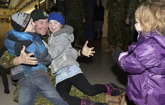 Major Drew Willis, a member from 2nd Battalion, The Royal Canadian Regiment, returning from Op PROVISION is reunited with his family Alexander (left), Madelyn (right) and Victoria (far right) at 5th Canadian Division Support Base Gagetown, January 12, 2016.  Operation PROVISION is the Canadian Armed Forces support to the Government of Canada's Syrian Refugee resettlement plan. Of the approximately 60 members returning at this time, the majority are from 2nd Battalion, The Royal Canadian Regiment (2RCR). They deployed to assist Immigration, Refugees and Citizenship Canada (IRCC) with the screening of refugees, including the provision of medical support, the collection of biometric data, and the processing of applicants.  Photo credit: MCpl Robert LeBlanc, 5th Cdn Div Public Affairs CAF Imagery Number: AX01-2016-0002-03 2016 DND-MND Canada