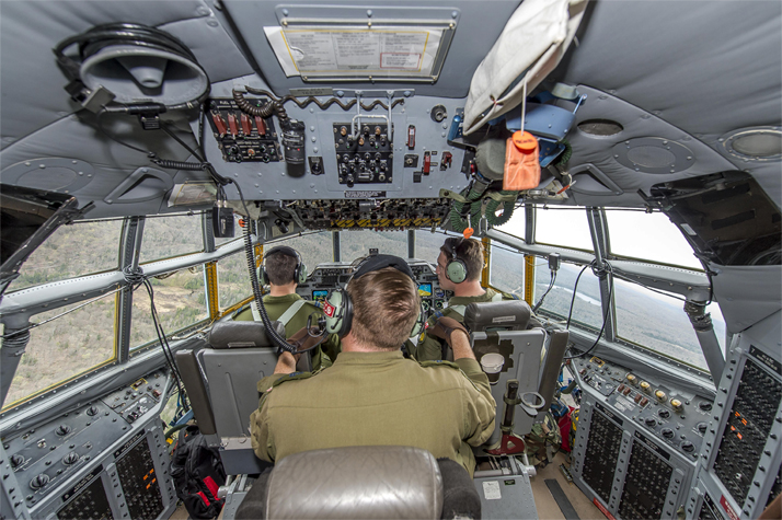 424 Transport and Rescue Squadron pilots, Captain Jeff McIsaac and Captain Dan Desjardins, and flight engineer, Master Corporal Mike Buggie, work in the CC-130H Hercules flight deck during TIGEREX 16 in Sault Ste. Marie, Ontario on May 12, 2016. Photo: Master Corporal Jonathan Barrette, Canadian Forces Combat Camera IS04-2016-0002-091