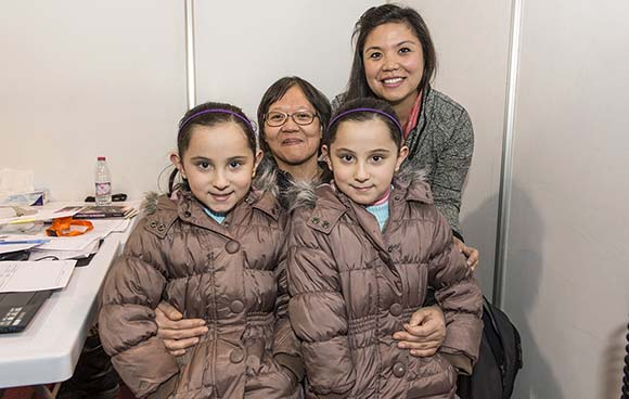 Commander Helen Kwan and Captain Iphigenia Stefatos pose with the identical twin daughters of Salah Malouhi at the processing centre in Amman, Jordan on December 31, 2015 during Operation PROVISION. Photo: MCpl Bernie Kuhn, Canadian Forces Joint Imagery Centre RE27-2015-9999-651