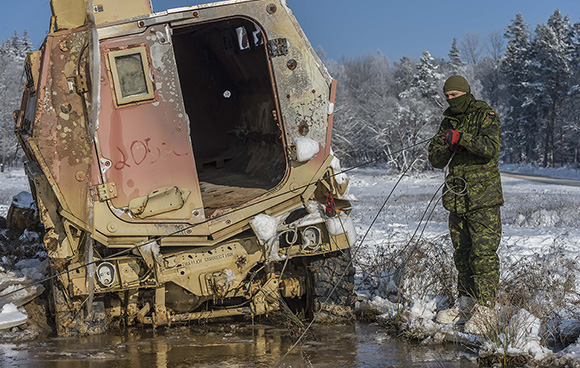 Corporal Matthieu Racette connects a pulley relay to a Canadian Armed Forces recovery vehicle during a vehicle recovery practice during Exercise ALLIED SPIRIT IV at the Joint Multinational Readiness Center Training area in Hohenfels, Germany on January 19, 2016 as part of Operation REASSURANCE.  Photo: Corporal Nathan Moulton, Land Task Force Imagery, OP REASSURANCE RP001-2016-0001-0060